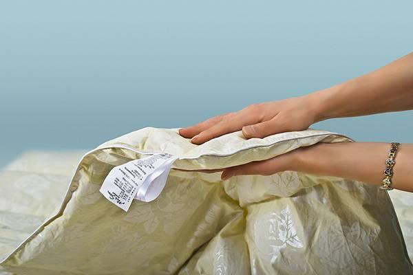 В руках часть одеяла. Стирать